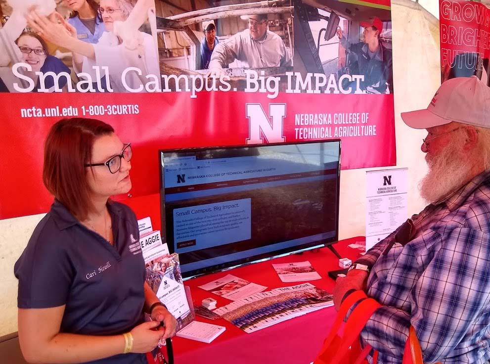 NCTA student Cari Howell of Lewiston, Nebraska visits with Doug Poland of Sargent at Husker Harvest Days. (Crawford/NCTA News photo)