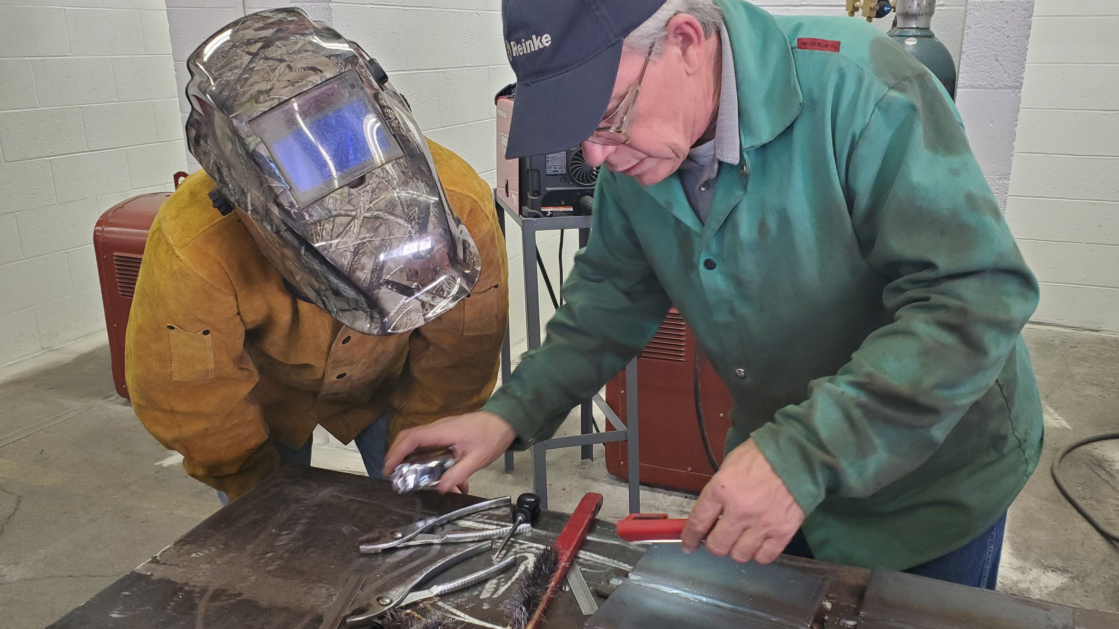 Chuck Hatzenbuehler of Reinke Manufacturing examines welds by Aggie Trever Muellenberg, North Platte, during a test for American Welding Society certification. (M. Crawford / NCTA photo)