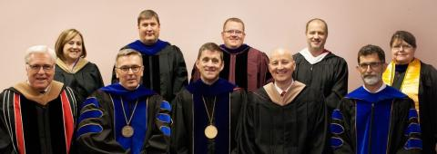 Faculty colleagues Dr. Doug Smith, center of second row, and Mary Rittenhouse, at right back row, joined standing, from left, Jennifer McConville, Dr. Brad Ramsdale and Eric Reed at the 2016 NCTA Commencement. Front row, from left, is Regent Bob Phares of North Platte, now-UNL Chancellor Ronnie Green (IANR VIce Chancellor last year), University President Hank Bounds, Nebraska Governor Pete Ricketts and NCTA Dean Ron Rosati.