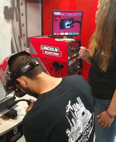 Amanda Schmidt, NCTA Ag Ed major with a welding emphasis, guides classmate Clancey Smith, ag mechanics major, on operation of a virtual welding simulator at Husker Harvest Days. The two were volunteers at a traveling trailer sponsored by the American Welding Society to encourage careers in welding trades. (Crawford/NCTA News photo)