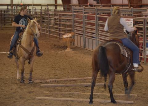 Annie Bassett (at left), NCTA Ranch Horse Team member from Ogallala, and her mare Annabelle gain pointers on how to side pass in a trail riding course with Huntra Christenson, assistant coach. (Crawford / NCTA photo)