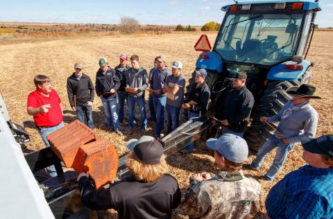 Agronomy professor Brad Ramsdale discusses seeding rate and grain drill calibrations with NCTA students at the college farm. (Craig Chandler / University Communication Photo)