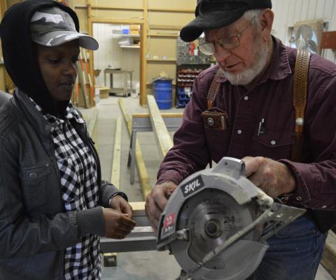 CUSP student Yvonne Ingabire receives safety instructions before operating a power saw in a construction class taught by Roy Cole. He designed a sheep shed which students are building for the NCTA campus farm. (Crawford/NCTA News)