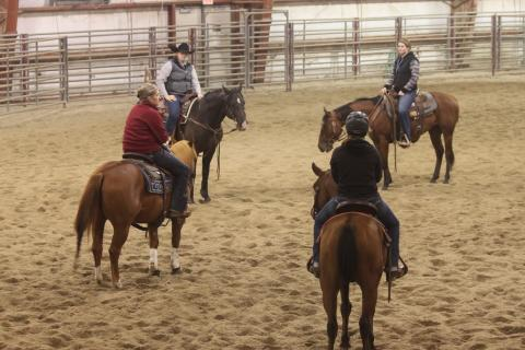 Professor Joanna Hergenreder meets with members of the NCTA Ranch Horse Team during a practice session in the indoor arena of Livestock Teaching Center on campus.  (Emily Grote photo / NCTA News