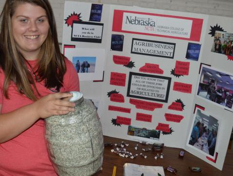 Kathryn Schick shows NCTA students what 8 pounds of shredded bills look like during a recent campus fair. (Crawford/NCTA News)