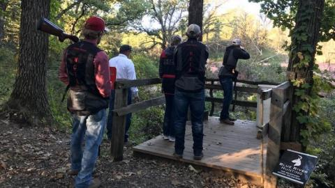 Trey Barnhart aims at clay targets with Aggie teammates and Coach Taylor watching. (Photo by Shotgun Sports athlete McKenna Darby)