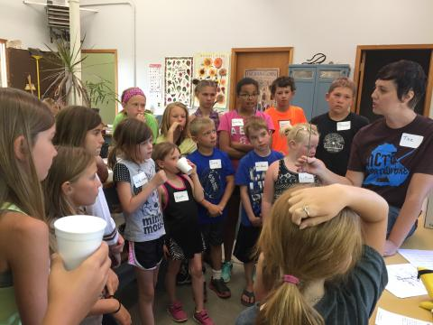 Tee Bush, far right, describes the parts of a plant to Clover Kids and area youth at the NCTA greenhouse. (Nebraska Extension-Frontier County photo)